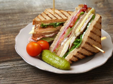 Photo of a club sandwich made with turkey, bacon, ham, tomato, cheese, lettuce, and garnished with a pickle and two cherry tomatoes. Imagens