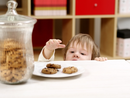 sneaky: Photo of a nineteen-month-old stealing cookies from a plate on a table with a full cookie jar beside.