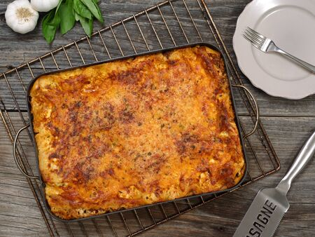 Photo of a freshly baked lasagna, sitting on an old wooden table. photo