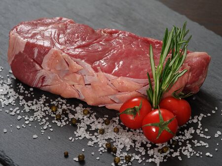sirloin steak:   a raw thick sirloin steak with rosemary, cherry tomatoes, salt and peppercorns on a piece of black slate.