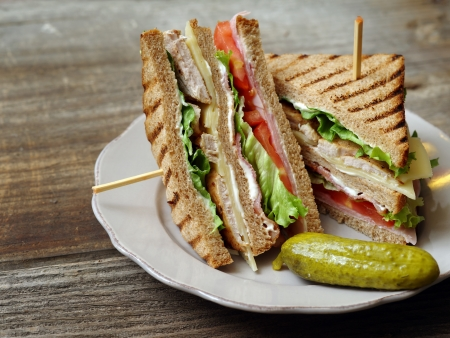 turkey bacon: Photo of a club sandwich made with turkey, bacon, ham, tomato, cheese, lettuce, and garnished with a pickle.