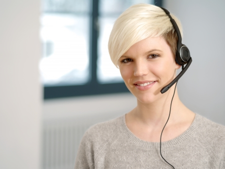 Photo of a cute young call center female with short blond hair and big smile wearing a headset. photo