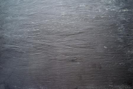 dark grey slate: Photo of a large background of rough slate rock.