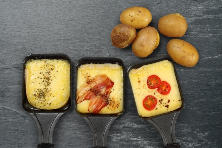 Photo of a three Raclette trays with melted cheese, herbs, cherry tomato, bacon, onion and potatoes on rough slate. Plenty of space for text.