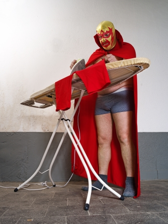 ironing board:  a Mexican wrestler or Luchador ironing his red tights before his fight. Stock Photo
