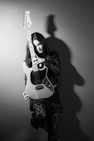 girl shadow: Photo of a female guitarist leaning up against a wall holding an electric guitar.