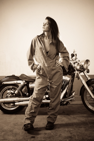 Photo of a beautiful female mechanic wearing overalls and standing in front of a motorcycle. photo