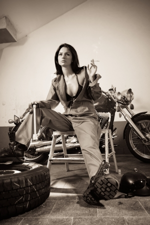 Photo of a beautiful female mechanic wearing overalls, leather bra, and sitting in front of a motorcycle smoking and holding a tool