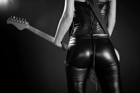 culo: Foto de la parte de atr�s de un guitarrista femenino de pie y jugar delante de un foco pel�cula grano a�adido Foto de archivo