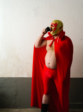 Photograph of a Mexican wrestler or Luchador drinking coffee before his fight.