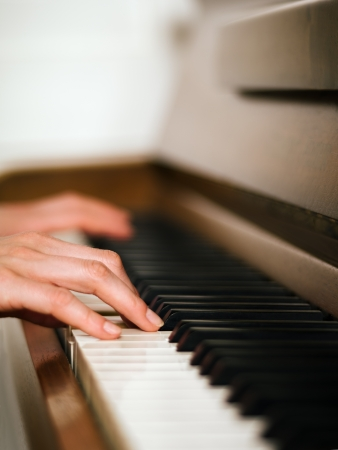 upright piano: Photo of female hands playing an upright piano  Very shallow depth of field with focus on fingers