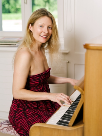 early thirties: Photo of a happy blond female in her early thirties playing the piano at home  Stock Photo