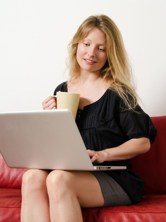 Photo of a beautiful young female shopping online and drinking coffee at home  Stock Photo - 21693924