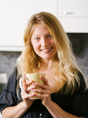 Photo of a beautiful smiling blond female in her kitchen holding a large coffee  Stock Photo - 21693961