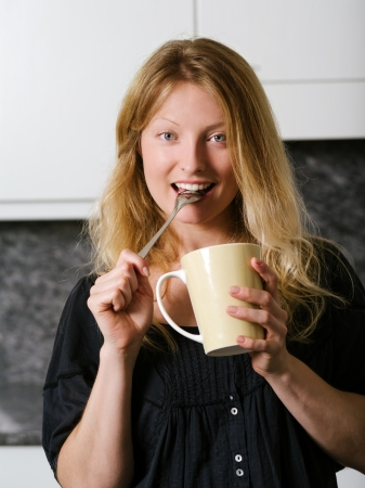 Photo of a beautiful blond holding a large coffee and a spoon in her mouth  Stock Photo - 21693962