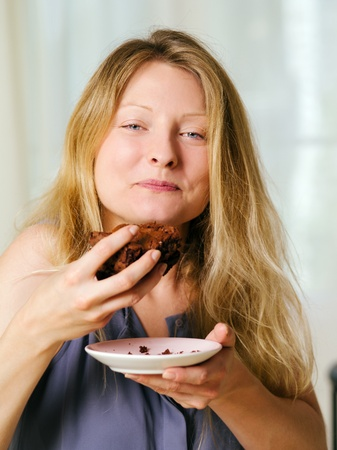 Photo of a beautiful blond woman in her early thirties with log blond hair eating a large piece of brownie or cake  photo