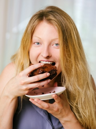 brownie: Photo of a beautiful blond woman in her early thirties with log blond hair eating a large piece of brownie or cake