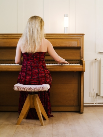 early thirties: Photo of a blond female in her early thirties playing the piano at home