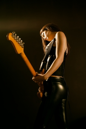 Photo of a young beautiful woman playing guitar on a dark stage with a spotlight on her face. photo