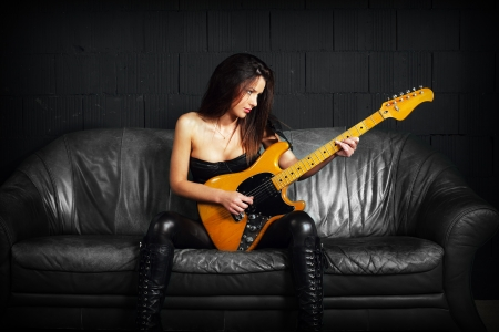 Photo of a sexy female guitar player wearing leather boots and sitting on old leather couch. Фото со стока