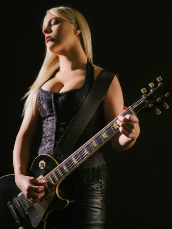 Photo of a sexy blond female playing a black electric guitar  photo