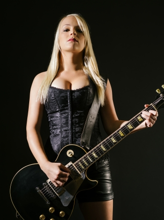 Photo of a sexy blond female playing a black electric guitar