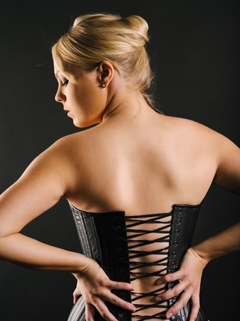 Photo of the back of a beautiful blond woman wearing a leather coset  photo