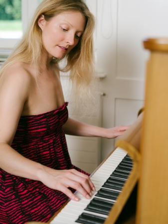 Photo of a happy blond female in her early thirties playing the piano at home  photo