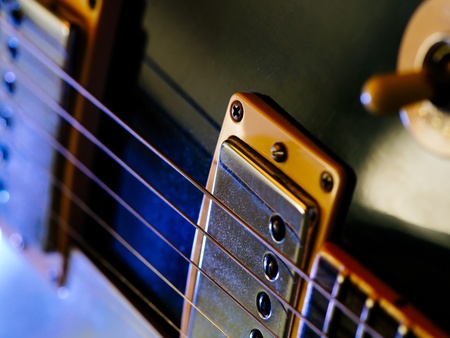 pickups: Macro abstract photo of the pickups and strings of an electric guitar  Shallow depth of field with focus on the first string