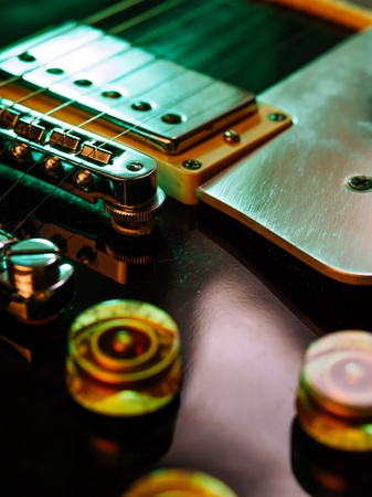 pickups: Macro abstract photo of the pickups, bridge and knobs of an electric guitar  Shallow depth of field with focus across the middle  Stock Photo