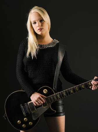 Photo of a sexy blond female playing a black electric guitar. Stock Photo - 22007647