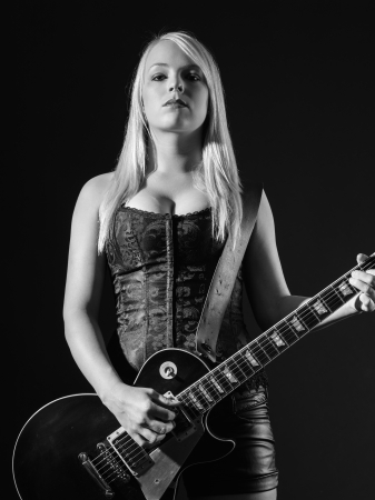 Photo of a sexy blond female playing a black electric guitar. photo
