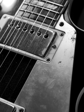 pickups: Macro abstract photo of the pickups and strings of an electric guitar.
