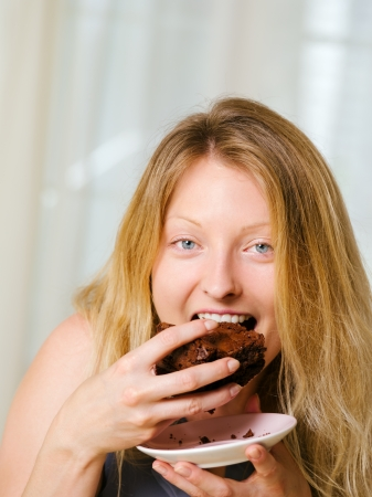 Photo of a beautiful blond woman in her early thirties with log blond hair eating a large piece of brownie or cake. photo