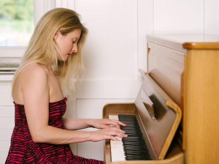 Photo of a happy blond female in her early thirties playing the piano at home.