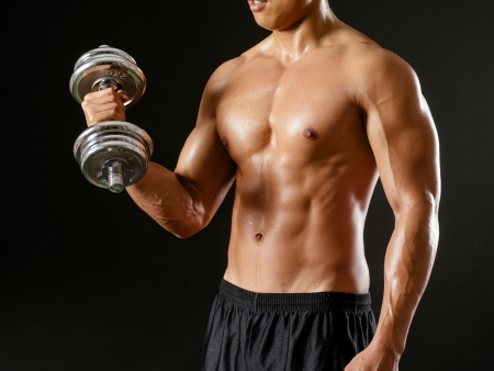 Photo of an Asian male exercising with dumbbells and doing bicep curls over dark background. Stock Photo