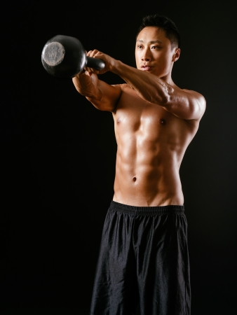 weightlifting equipment: Photo of an Asian male exercising with a kettle bell over dark background.