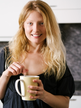 Photo of a beautiful blond holding a large coffee. Stock Photo - 22576981
