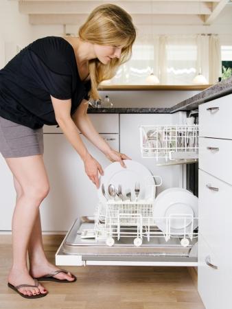 lavavajillas: Foto de una mujer rubia que se inclina sobre y descarga de su lavavajillas. Foto de archivo