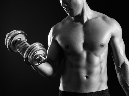 curls: Photo of an Asian male exercising with a dumbbell and doing bicep curls over dark background.