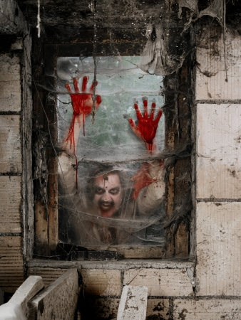 Photo of a hungry zombie staring at you through a dirty window.