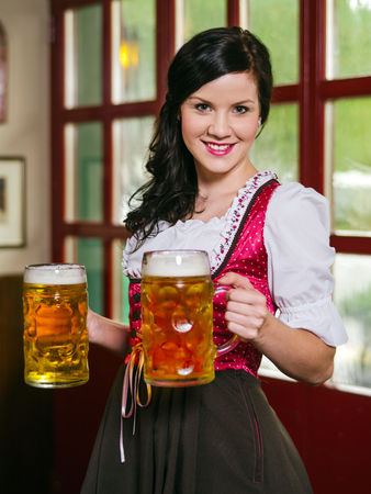 Photo of a beautiful female waitress wearing traditional dirndl and holding huge beers in a pub. photo