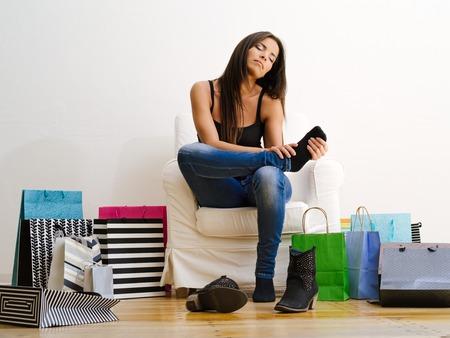 아픈: 쇼핑 가방과 그녀의 아픈 다리를 마찰에 의해 포위의 자에 앉아 젊은 아름 다운 여성의 사진. 스톡 사진
