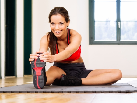 Photo of a beautiful female stretching on the floor sitting on a mat. Stock Photo