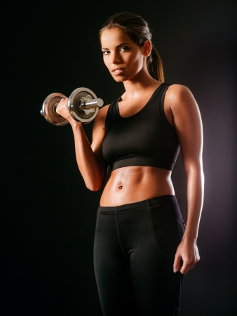 woman black background: Photo of a toned young female exercising with dumbbells. Stock Photo