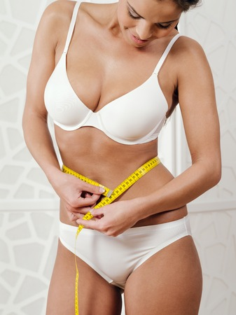 woman measuring: Photo of a slim young woman in her underwear measuring her waist with a tape measure.