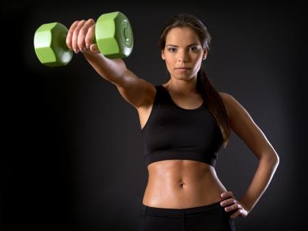 mujer deportista: Foto de una hermosa mujer haciendo una mosca delantera del hombro con una pesa sobre un fondo oscuro.