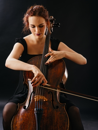 cello: Photo of a beautiful female musician playing a cello
