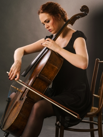 Photo of a beautiful female musician playing a cello