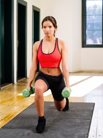 lunges: Photo of a beautiful female doing lunges with dumbbells  Stock Photo